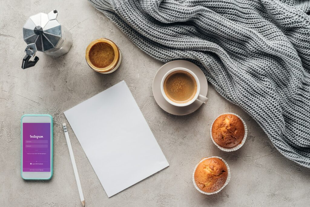 top view of cup of coffee with muffins, blank paper and smartphone with instagram app on screen on